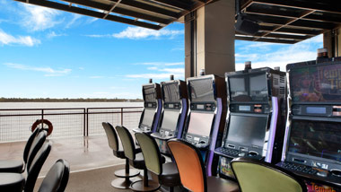 View past the slot machines to the the river from inside the Riverbend Gaming/Smoking Terrace at L